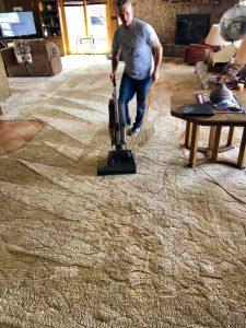 man vacuuming his carpets in San Diego